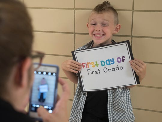 Students on the first day of first grade get their pictures taken at Allen Elementary.