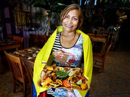 Mi Tierra co-owner Mirna Garcia displays the Columbia-Mexican cuisine restaurant's signature dish Picada Complete. The Summer Avenue eatery will celebrate it's 14th anniversary on this year's Holloween night.