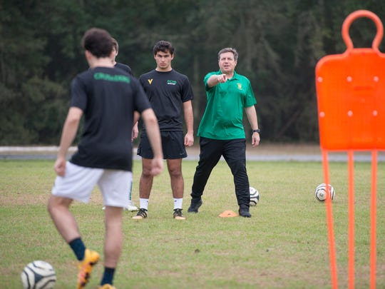 Head coach Del Greatwood, right, gives instructions during soccer practice at Pensacola Catholic High School on Thursday, January 11, 2018.