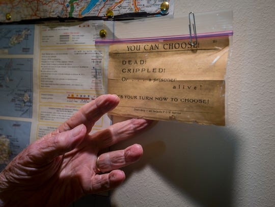 Richard Peterson shows a leaflet dropped by the WWII