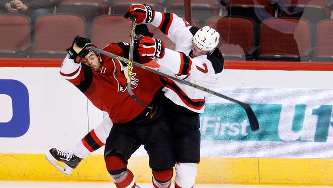 Jordan Martinook (left) of the Coyotes and Jon Merrill of the Devils slam into each other during the first period of an NHL game at Gila River Arena in Glendale on Saturday, January 16, 2016.