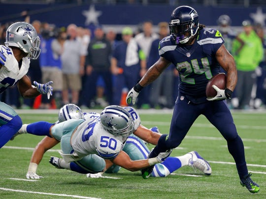 Seattle Seahawks running back Marshawn Lynch (24) breaks through a tackle-attempt by Dallas Cowboys' Sean Lee (50) as Cowboys Byron Jones, left, comes over to help on the running play in the second half of an NFL football game, in Arlington, Texas. Lynch, the mercurial Seattle Seahawks running back, sent a tweet during the fourth quarter of Sunday's Super Bowl with a pair of cleats hanging from a power or telephone line, along with an emoji depicting a peace sign. It certainly wasn't a definitive statement that Lynch is ready to call it a career, but it would fit with a mounting stack of evidence that the bruising running back is ready to move on from football.