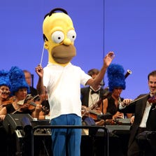 """The orchestra, led by conductor Thomas Wilkins in a Homer Simpson costume, performs at the world premiere of """"The Simpsons Take the Bowl"""" at the Hollywood Bowl in Los Angeles. The program featured music, stars and reminiscences from TV's longest-running scripted show."""