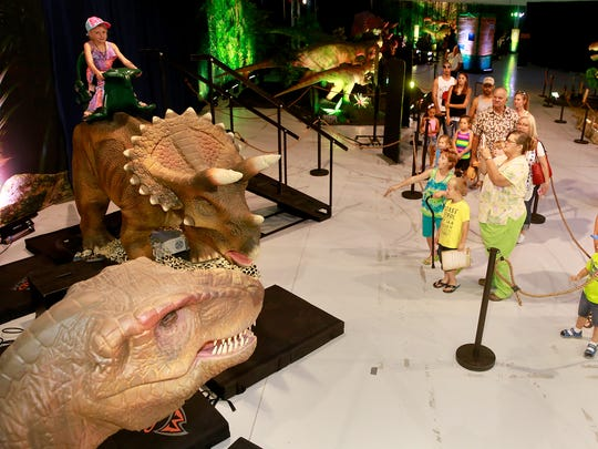 Families take in the Discover the Dinosaurs Unleashed exhibit on Saturday at the McGee Park Convention Center.