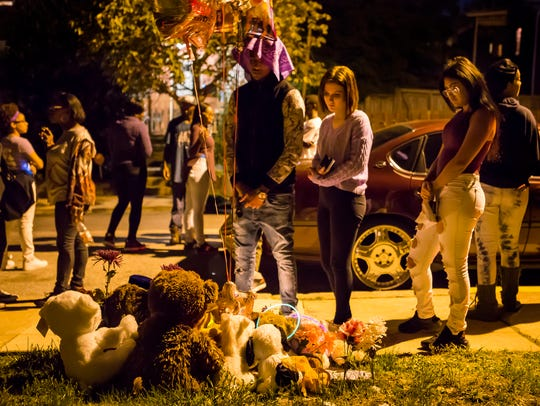 "Friends of Keshall ""KeKe"" Anderson look at stuffed animals and balloons left near the spot where she was killed along West 20th Street in Wilmington at a vigil commemorating her 20th birthday in 2016."