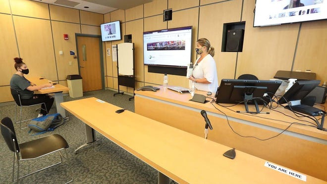 Lisa Rhoades leads an English literature class in fiction Monday with her one in-class student, Nadia Bess, 17, and the others online as seen on the screens at the University of Akron.