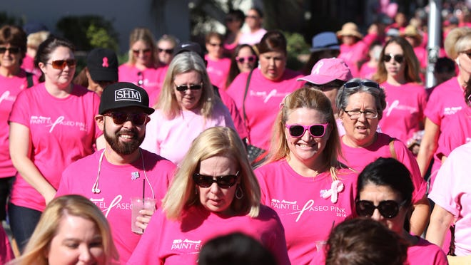People walk in the Desert Cancer Foundation's annual Paint El Paseo Pink event along El Paseo in Palm Desert on Saturday morning.