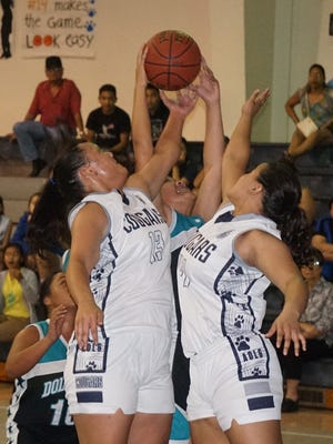 Academy of Our Lady of Guam forwards Meaghan Cruz, left, and Uriyah Tobiason battle for a rebound during the third quarter of the Cougars' Independent Interscholastic Athletic Association of Guam Girls' Basketball League home game against the Southern High Dolphins on Friday, Nov. 27.