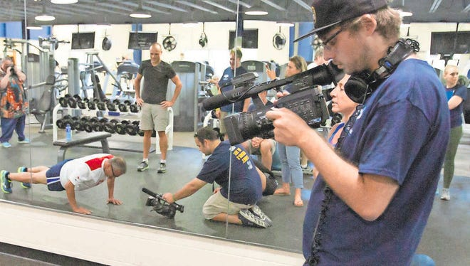 """A camera crew film a blind veteran working at the Hamburg Fitness Center as part of a Keith Famie documentary titled """"Death is NOT the Answer."""""""