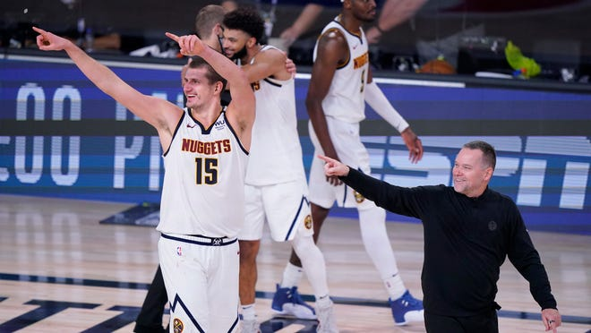Nuggets center Nikola Jokic (15) and coach Michael Malone, right, celebrates their win over the Clippers on Tuesday night.