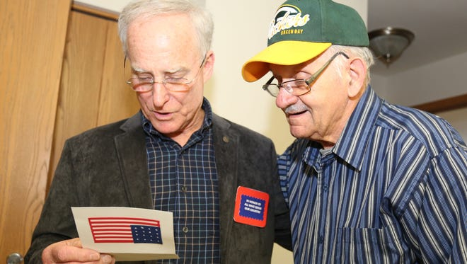 Veteran Tony Fessler, left, reads a thank you note to veteran David Guiliani of Sheboygan during his Meals on Wheels meal delivery Wednesday November 11, 2015, in Sheboygan.