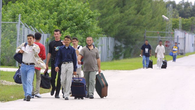 Foreign nationals drag their luggage behind them as they are released from the Krome Detention Center in Miami, Florida.