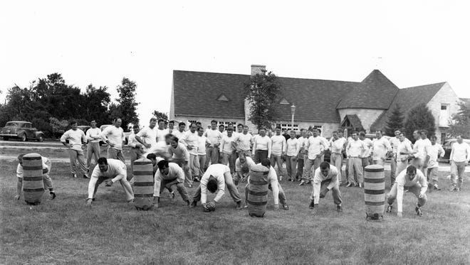 Green Bay Packers founder and head coach Curly Lambeau (center in dark pants) puts the team through a practice in front of Rockwood Lodge. The team bought the site in 1946.
