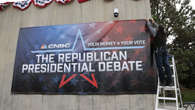 University of Colorado facilities management employees Robert Schumaker, right, and Jon Klarich put up a banner outside the Coors Events Center, the venue for the Oct. 28 Republican presidential debate, at CU Boulder, Colo., Monday Oct. 26, 2015.