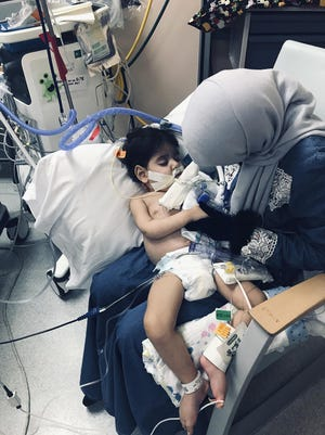Shaima Swileh holds her dying 2-year-old son Abdullah at a hospital in Oakland, Calif. Swileh, a Yemeni mother who fought for the right to see her dying son, arrived Wednesday night after the Trump administration gave her a long-sought waiver to its travel ban.