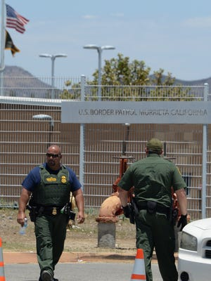 US Border patrol agents keep watch outside the entrance to the US Border Patrol facility in Murrieta during an anti-immigration protest in Murrieta, Calif., on July 7.