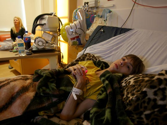 With his mom Trishann Cruickshank nearby 14-year-old Kaden Cook from Sault Ste. Marie lays in a hospital bed at C.S. Mott Children's Hospital in Ann Arbor on Saturday, Jan. 10, 2015 watching TV.