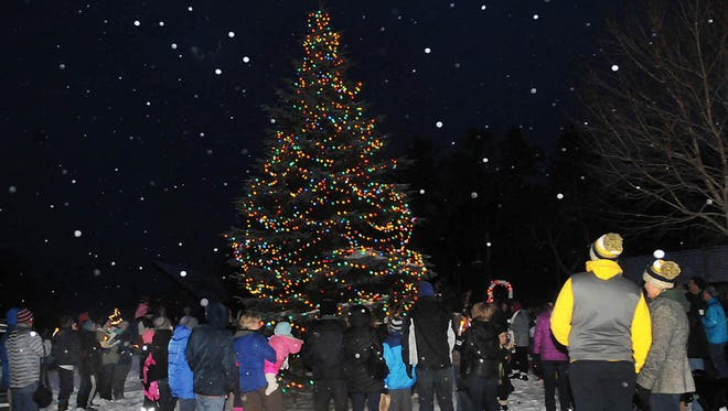 """Light snow gave a peaceful seasonal feeling as it drifted down upon the more than 100 people gathered around the Sister Bay holiday tree in Waterfront Park during last year's """"Capture the Spirit'' celebration."""