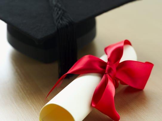 Close-up of a graduation cap and a diploma with ribbon
