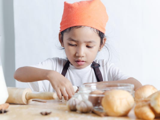 Portrait of Asian little girl holding dough in hand and bakery on the wooden table over the white background