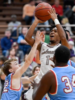 Henderson's Cartel Gilbert (1) puts a shot up against defense from Union County's Daniel Steward (12) and Union County's Marqualio King (34) as the Henderson County Colonels play district rival the Union County Braves at Colonel Gym Monday, January 22, 2018.