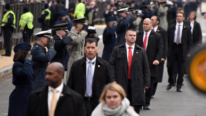 Secret Service agents walk the parade route as President Donald J. Trump's motorcade moves along.