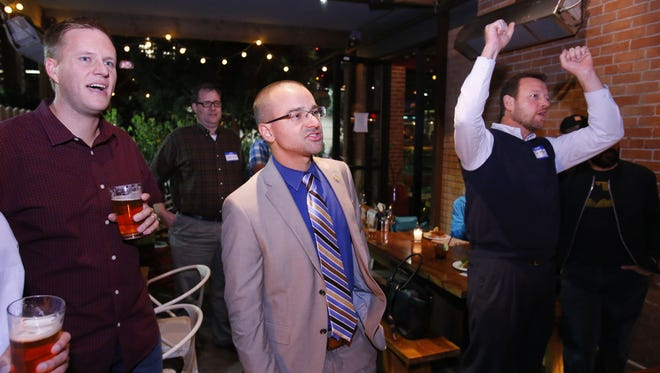 Interim Superintendent Chad Gestson, center, celebrates with supporters as early election results come in for the  Phoenix Union High School District's capital override request, Tuesday Nov. 3, 2015 at the Phoenix Public Market Cafe in Phoenix , Ariz.