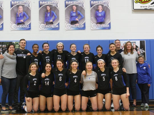 Mother of Mercy's volleyball team poses for a photo after the final match ever to be played in Mercy's gym on Oct. 12, 2017.
