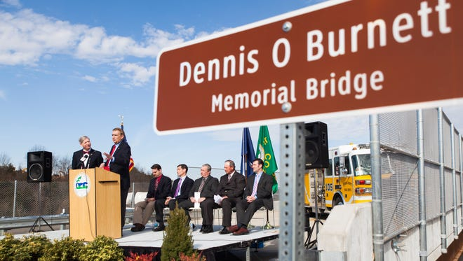 Standing beside Del. Steve Landes, left, State Sen. Emmett Hanger addresses the crowd gathered at the bridge dedication ceremony on Lifecore Drive remembering the legacy of Dennis Burnett in Fishersville on Friday, March 13, 2015.