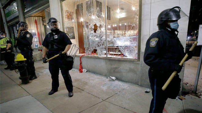 Police officers stand in front of a business with a broken window in Boston, Sunday, May 31, 2020, following a march and gathering to protest the death of George Floyd, who died after being restrained by Minneapolis police officers on May 25.