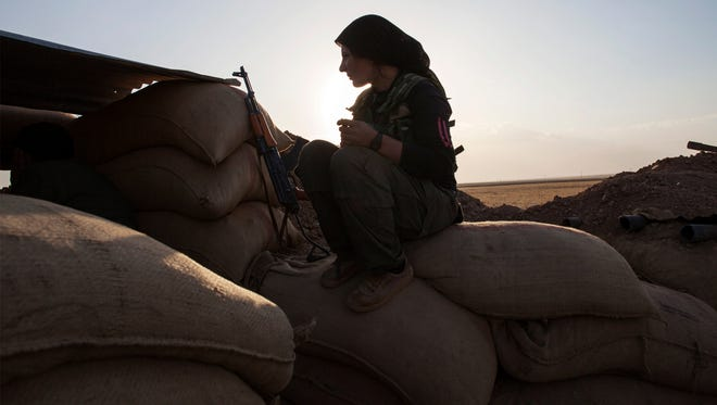A fighter of the Kurdish of the Kurdish Women's Defense Units sits on sand bags as she holds a position on the front line on Oct. 19, 2013, in Derik near the border between Turkey and Iraq.