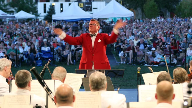 The Cincinnati Pops Orchestra, conducted by John Morris Russell, performs during Lumenocity at Washington Park in 2013.