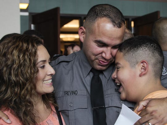 Jesus Trevino, of Saginaw, hugs with son Vincent, 11, and wife, Natalie, on Friday after he and 268 others were honored as new corrections officers during the Michigan Department of Corrections commencement ceremony at the Lansing Center in downtown Lansing.