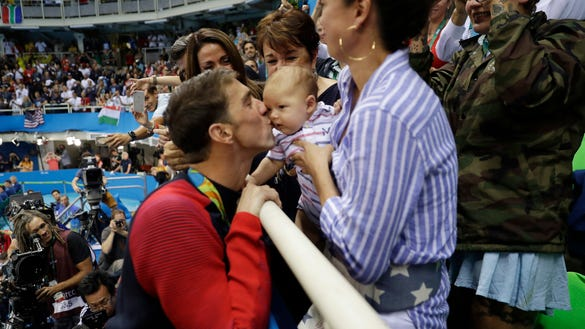 Michael Phelps kisses his son, Boomer, during the Rio
