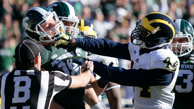 Michigan's Delano Hill, right, shoves Michigan State quarterback Connor Cook on Oct. 25, 2014, in East Lansing.