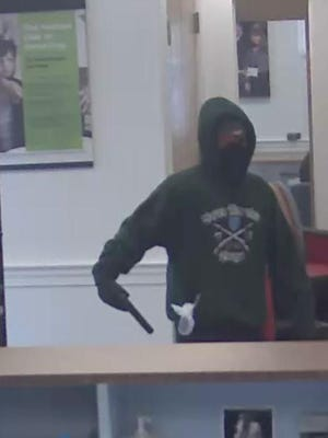 Bank photo shows man with mask demanding money at the TD Bank in St. Albans.