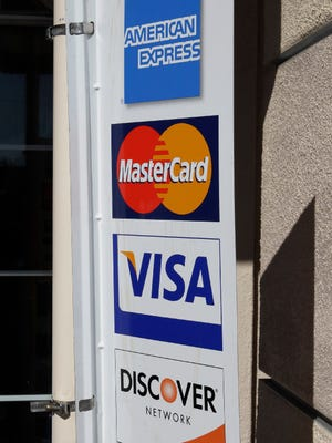 In this Jan. 18, 2011, file photo, four major credit cards advertise at a restaurant in Millbrae, Calif. The math behind your credit score is getting an overhaul, with changes that may alter the behavior of both cautious spenders and riskier borrowers.