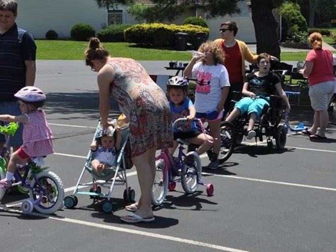 """Riders and operators of bicycles, strollers, wheelchairs and scooters line up to receive prayers for safety at the """"All Wheels Welcome"""" Motorcycle Blessing at Clough United Methodist Church June 1."""