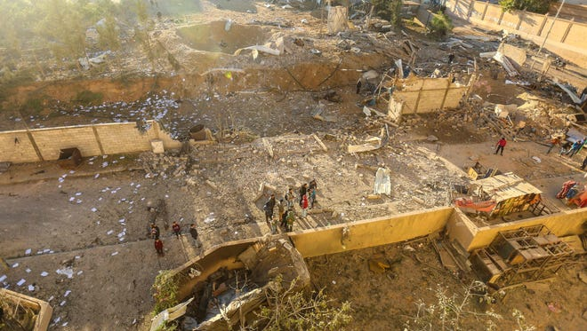 Palestinians look at the damage at a Hamas military facility in the aftermath of an Israeli airstrike early Saturday.