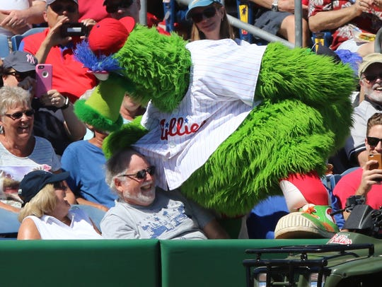 The Phillie Phanatic climbs into the stands to joke