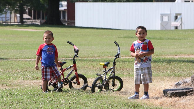 The Jaimes brothers, Raul, 3, left, and Ruben, 4, take a break from their bike ride around the Fort Smith National Historic Site, Tuesday, June 16, 2020, during a visit with their mother, Lorena Jaimes and sisters, Yanellie, 7, and Natalie, 8.