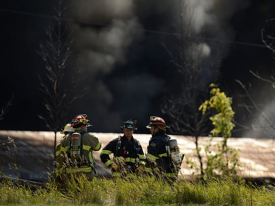 A blanket of smoke fills the sky as firefighters from