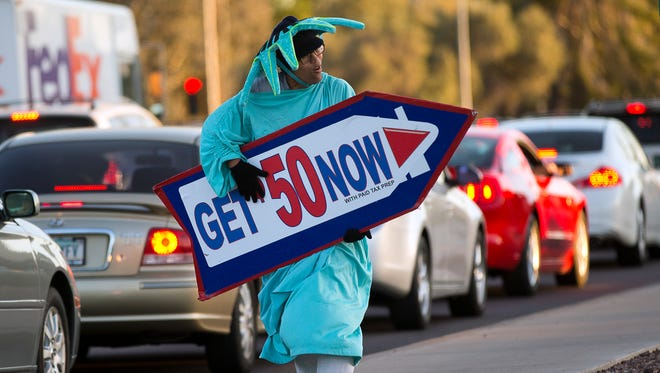 Darien Kiem holds a sign advertising Liberty Tax Service near Hayden and Thomas roads in Scottsdale on Feb. 10, 2014.