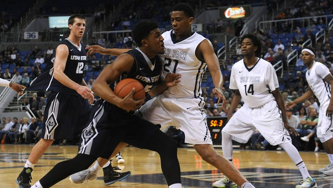 Nevada's Eric Cooper Jr. (21) defends against Utah State's Julion Pearre (5) during their basketball game at Lawlor Events Center in Reno on Wednesday.