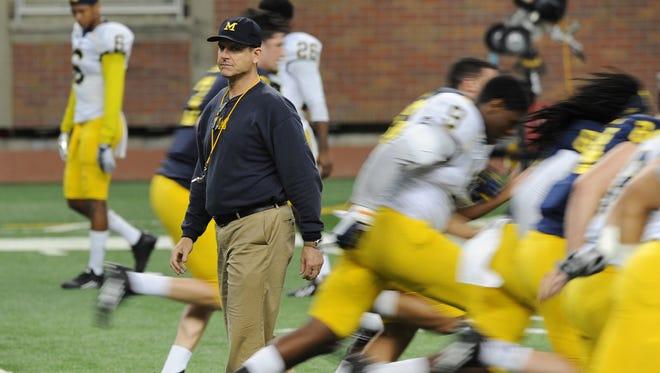 Michigan coach Jim Harbaugh overlooks drills Saturday at Ford Field.