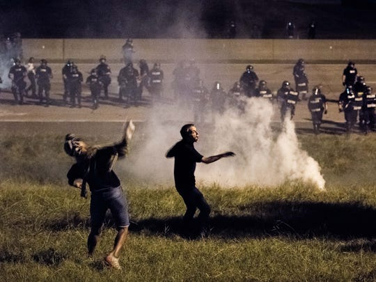 CHARLOTTE, NC - SEPTEMBER 21: Protestors throw objects at police officers on the I-85 during protests.