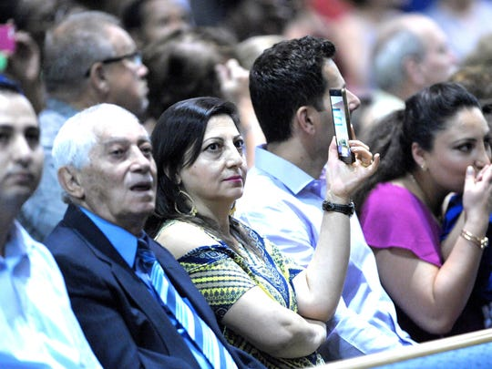 Officer Fadi Shukur's sister, Anita Banks, center, records the August 18, 2017 Detroit Police graduation while sitting with her father, Zia Hanna, second from left, and other family members.
