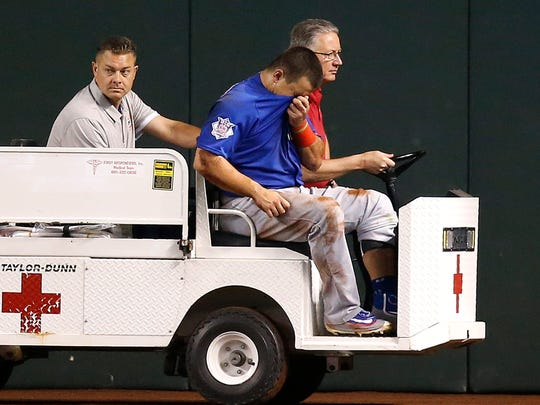 An injured Chicago Cubs' Kyle Schwarber, front, is taken off the field against the Arizona Diamondbacks  April 7, 2016, in Phoenix.
