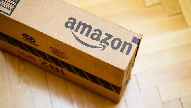 Paris, France - January 28, 2016: Amazon logotype printed on cardboard box side seen from above on a wooden parwuet floor. Amazon is an American electronic e-commerce company distribution worlwide e-commerce goods