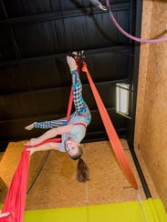 A student hangs upside down on silks at Flyhouse Circus